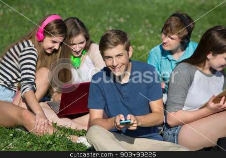 Male Teen Texting stock photo, Group of cheerful students texting and studying by Scott Griessel