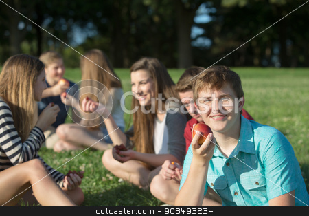 Grinning Youth With Apple stock photo, Happy group of teenagers eating healthy snacks outdoors by Scott Griessel