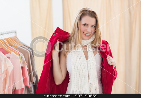 Smiling young blonde woman trying a jacket stock photo, Smiling young blonde woman trying a jacket in the store by Wavebreak Media
