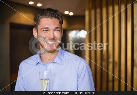 Handsome man holding flute of champagne stock photo, Handsome man holding flute of champagne at the bar by Wavebreak Media