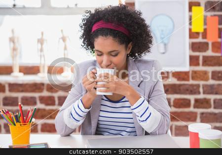 Interior designer drinking coffee at desk stock photo, Female interior designer drinking coffee at office desk by Wavebreak Media