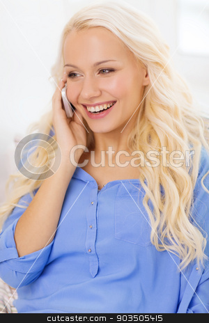 smiling woman with smartphone at home stock photo, home, technology and communication concept - smiling woman with smartphone lying on couch at home by Syda Productions