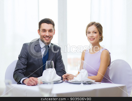 smiling couple at restaurant stock photo, restaurant, couple and holiday concept - smiling couple at restaurant by Syda Productions