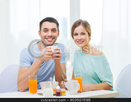 smiling couple having breakfast at home stock photo, food, home, couple and happiness concept - smiling couple having breakfast at home by Syda Productions