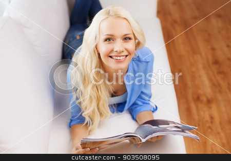 woman lying on couch and reading magazine at home stock photo, home and leasure concept - smiling woman lying on couch and reading magazine at home by Syda Productions