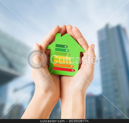 hands holding green paper house stock photo, energy saving, real estate and family home concept - closeup of female hands holding green paper house with energy efficiency rating by Syda Productions