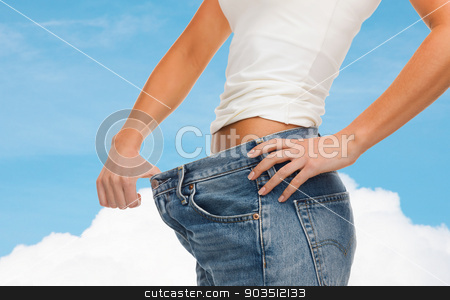 close up of female showing big jeans stock photo, healthcare, diet and fitness concept - close up of female showing big jeans by Syda Productions