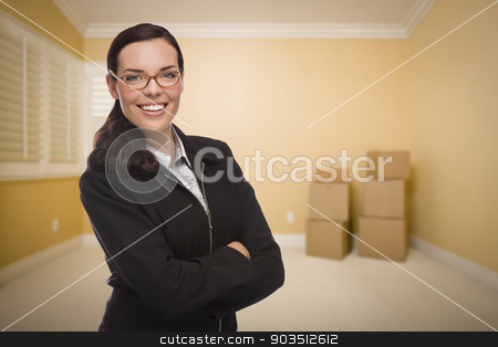 Mixed Race Woman in Empty Room with Boxes stock photo, Attractive Confident Mixed Race Woman in Empty Room with Boxes. by Andy Dean