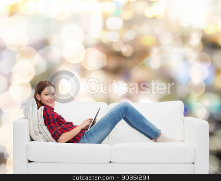 teenage girl sitting on sofa with tablet pc stock photo, technology and happy people concept - teenage girl sitting on sofa with tablet pc by Syda Productions