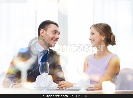 smiling couple looking at each other at restaurant stock photo, restaurant, couple and holiday concept - smiling couple looking at each other at restaurant by Syda Productions