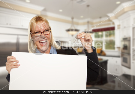 Young Woman Holding Blank Sign and Keys Inside Kitchen stock photo, Happy Young Woman Holding Blank Sign and Keys Inside Beautiful Custom Kitchen. by Andy Dean