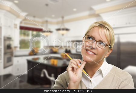 Daydreaming Woman with Pencil Inside Beautiful Custom Kitchen stock photo, Attractive Daydreaming Woman with Pencil Inside Beautiful Custom Kitchen. by Andy Dean