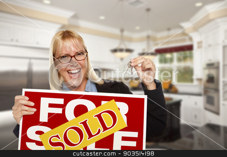 Young Woman Holding Sold Sign and Keys Inside New Kitchen stock photo, Happy Young Woman Holding Sold For Sale Real Estate Sign and Keys Inside Beautiful Custom Kitchen. by Andy Dean