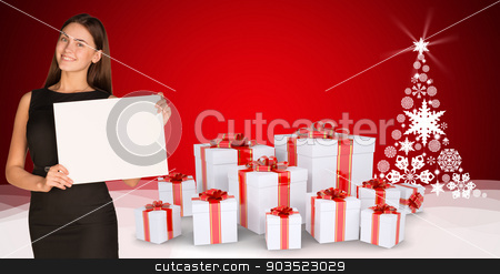 Businesswoman holding empty paper with christmas tree and gifts stock photo, Businesswoman holding empty paper. Christmas tree and gifts as backdrop by cherezoff