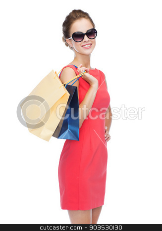 smiling elegant woman in dress with shopping bags stock photo, shopping, sale, christmas and holiday concept - smiling elegant woman in red dress and sunglasses with shopping bags by Syda Productions