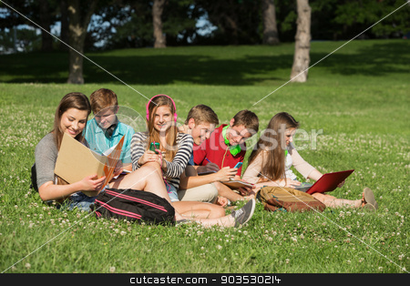 Students Doing Homework stock photo, Cute group of students with books and laptop working outdoors by Scott Griessel
