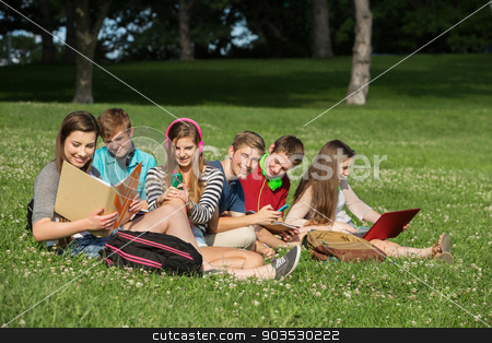 Cheerful Students Doing Homework stock photo, Cheerful students with books and laptop working outdoors by Scott Griessel