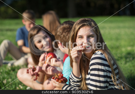 Girl with Braces Eating Grapes stock photo, Cute young female eating grapes with group outdoors by Scott Griessel