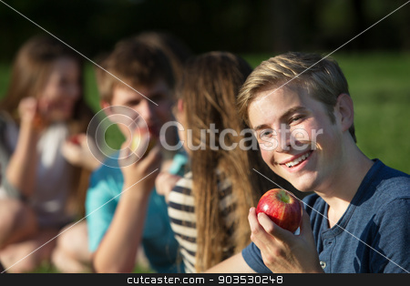 Happy Youth with Apple stock photo, Smiling Caucasian teenager hold red delicious apple  by Scott Griessel