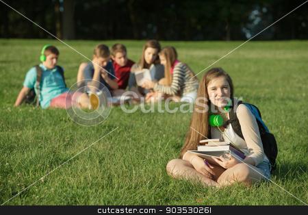 Cute Teen Sitting Near Group stock photo, Cute female teenage student sitting near group outdoors by Scott Griessel