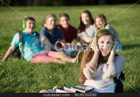 Student Singing Out Loud stock photo, Happy female student with headphones singing outdoors by Scott Griessel
