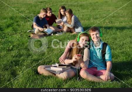 Teen Couple Sitting Outdoors stock photo, Cheerful European couple with earphones and cell phone outdoors by Scott Griessel