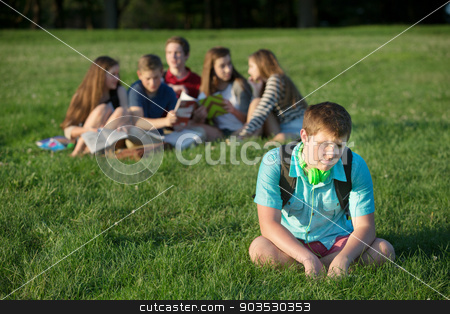 Sad Teen Outdoors stock photo, Lonely teen male sitting away from group by Scott Griessel