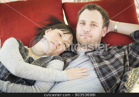 Mixed Race Couple Relaxing in a Hammock stock photo, Happy Mixed Race Couple Relaxing in a Hammock Outside. by Andy Dean