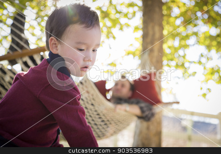 Mixed Race Boy Having Fun While Parent Watches From Behind stock photo, Mixed Race Boy Having Fun Outside While Parent Watches From Behind in a Hammock. by Andy Dean
