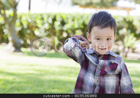 Mixed Race Boy Playing Football Outside stock photo, Adorable Mixed Race Boy Playing Football Outside at the Park. by Andy Dean