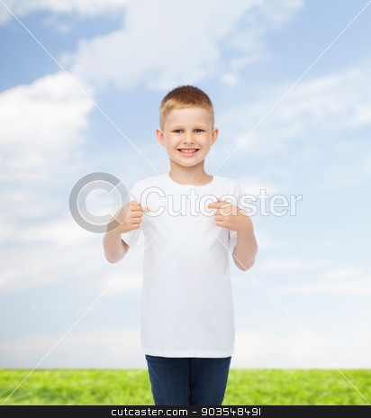 smiling little boy in white blank t-shirt stock photo, advertising, people and childhood concept - smiling little boy in white blank t-shirt pointing fingers at himself over natural background by Syda Productions
