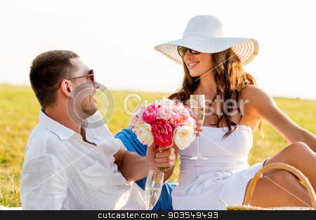 smiling couple drinking champagne on picnic stock photo, love, dating, people and holidays concept - smiling couple drinking champagne on picnic by Syda Productions