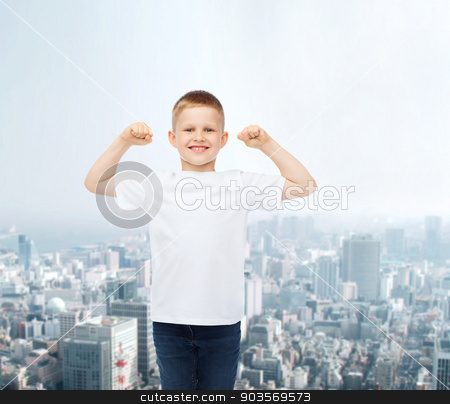 smiling little boy in white blank t-shirt stock photo, advertising, people and childhood concept - smiling little boy in white blank t-shirt with raised hands over city background by Syda Productions