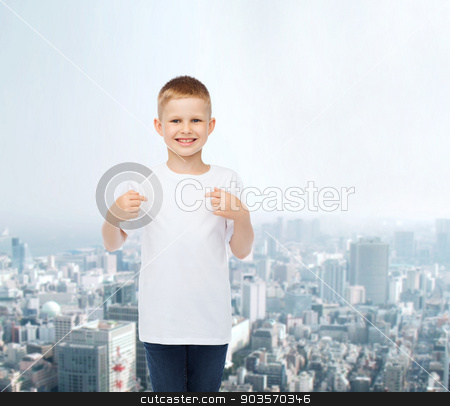 smiling little boy in white blank t-shirt stock photo, advertising, people and childhood concept - smiling little boy in white blank t-shirt pointing fingers at himself over city background by Syda Productions