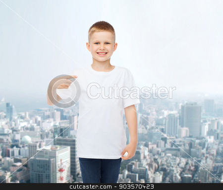 smiling little boy in white blank t-shirt stock photo, advertising, people and childhood concept - smiling little boy in white blank t-shirt pointing finger at himself over city background by Syda Productions