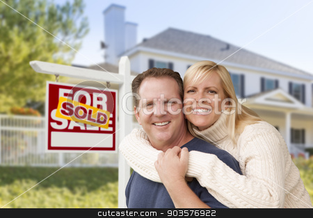 Couple in Front of New House and Sold Sign stock photo, Affectionate Happy Couple in Front of New House and Sold For Sale Real Estate Sign. by Andy Dean