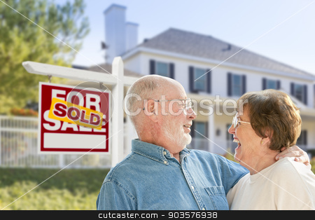 Senior Couple in Front of Sold Real Estate Sign, House stock photo, Happy Affectionate Senior Couple Hugging in Front of Sold Real Estate Sign and House. by Andy Dean