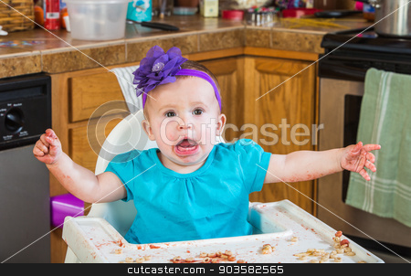 Messy Child Eating Tantrum stock photo, A talkative baby girl eating in the kitchen by Scott Griessel