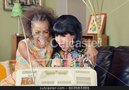 Pair of Ladies Laughing at TV stock photo, Mixed pair of friends laughing together in front of television by Scott Griessel