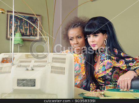 Serious Ladies Watching TV stock photo, Two serious Black and Caucasian friends watching retro television by Scott Griessel