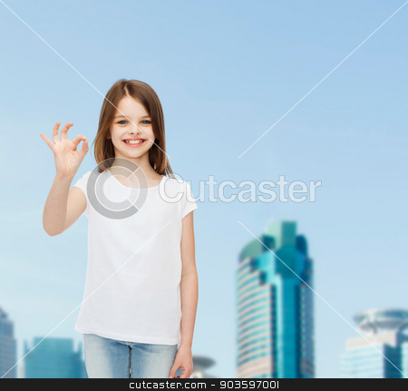 smiling little girl in white blank t-shirt stock photo, advertising, childhood, city, gesture and people concept - smiling girl in white t-shirt showing ok sign over business center background by Syda Productions
