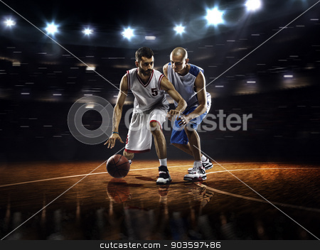 Two basketball players in action stock photo, Two basketball players in action in gym in lights by Eugene Onischenko