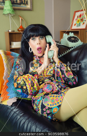 Startled Female Covering Phone stock photo, Startled woman in paisley dress covering telephone by Scott Griessel
