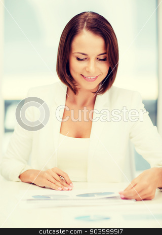 businesswoman working with graphs in office stock photo, business concept - businesswoman working with graphs in office by Syda Productions