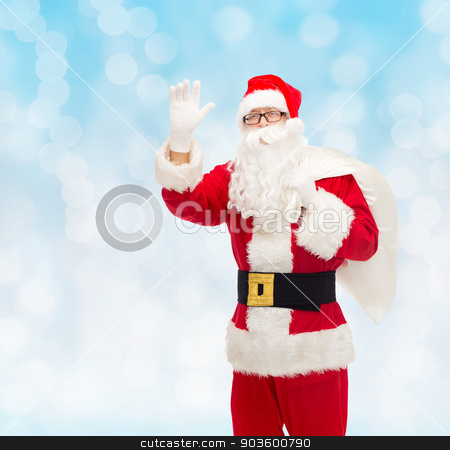 man in costume of santa claus with bag stock photo, christmas, holidays, gesture and people concept - man in costume of santa claus with bag waving hand over blue lights background by Syda Productions