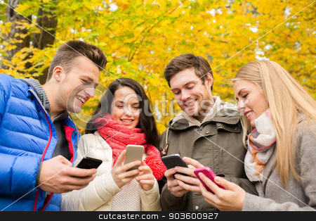 smiling friends with smartphones in city park stock photo, season, people, technology and friendship concept - group of smiling friends with smartphones in autumn park by Syda Productions