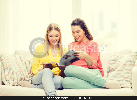 two girlfriends reading magazine at home stock photo, friendship and happiness concept - two girlfriends reading magazine at home by Syda Productions