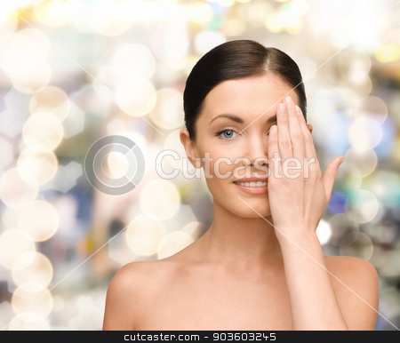 smiling young woman covering face with hand stock photo, beauty, people and health concept - smiling young woman covering half of face with hand over lights background by Syda Productions