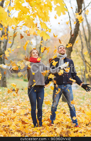 smiling couple having fun in autumn park stock photo, love, relationship, family, season and people concept - smiling couple throwing leaves and having fun in autumn park by Syda Productions