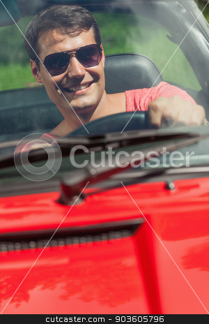 Cheerful handsome man driving his cabriolet stock photo, Cheerful handsome man driving his cabriolet on a sunny day by Wavebreak Media